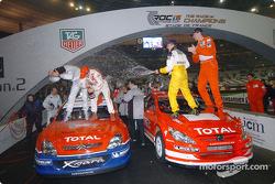 Heikki Kovalainen and Marcus Gronholm spray champagne at Jean Alesi and Sébastien Loeb