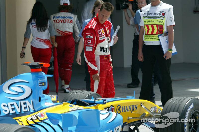 Michael Schumacher inspecciona el Renault F1 de Fernando Alonso
