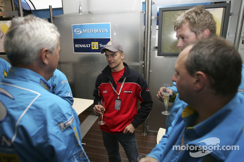 Heikki Kovalainen has a sip of champagne in the Renault F1 garage area