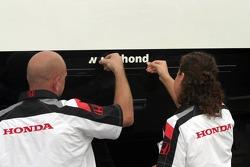 BAR-Honda team members remove a sticker from a transporter