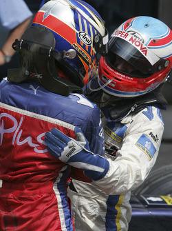 Race winner Heikki Kovalainen celebrates with Adam Carroll