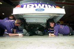 Crewmen working  under the #26 car