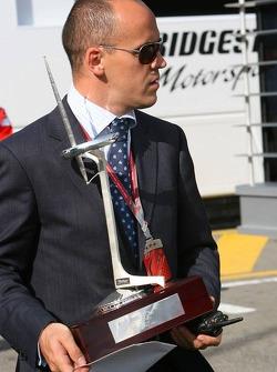 A man brings the Formula 1 winners trophy into the Formula 1 paddock