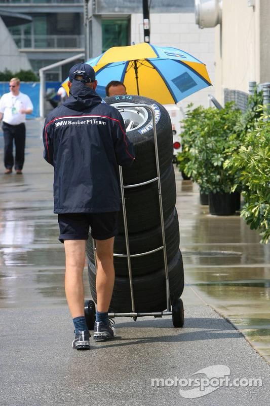 Un membre de l'équipe BMW Sauber F1 pousse des pneus dans le paddock