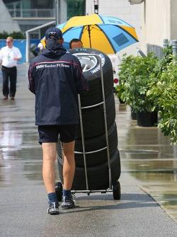 BMW Sauber F1 team member pushes tires through the paddock