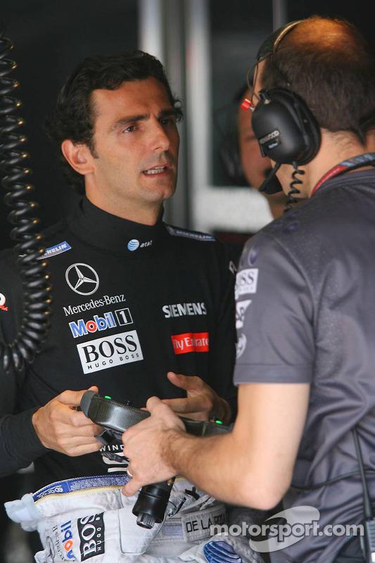 Pedro de la Rosa parle avec un ingénieur de McLaren Mercedes au sujet du volant des voitures