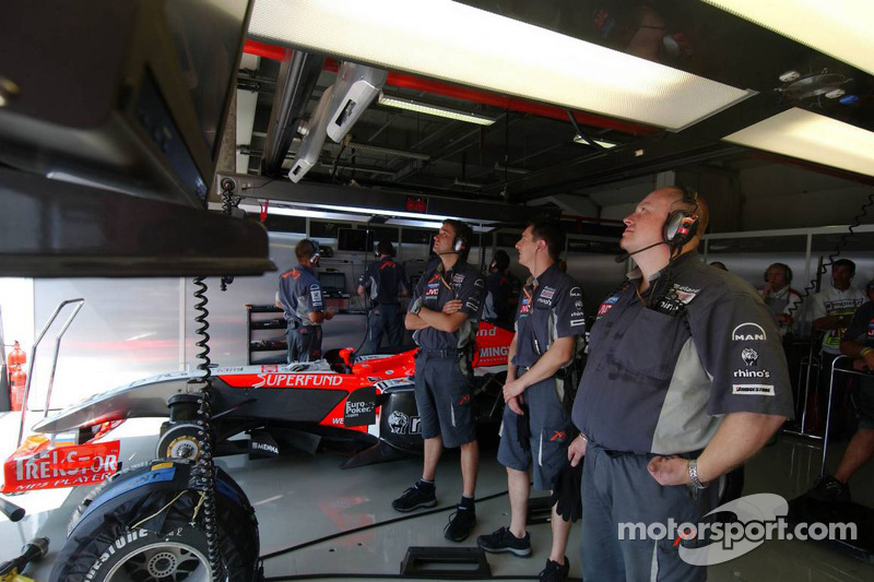 Des mécaniciens regardent la course sur l'écran TV