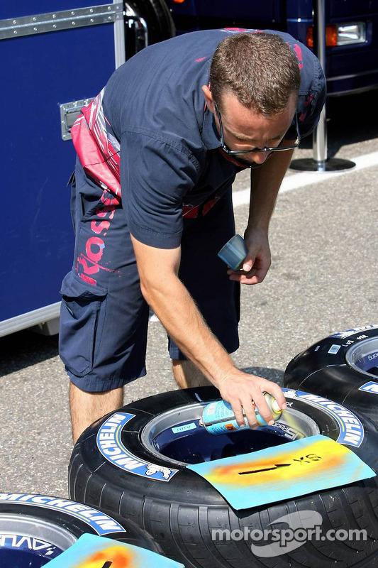 L'équipe Scuderia Toro Rosso met de la peinture sur les pneus Michelin