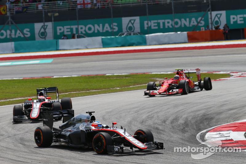 Fernando Alonso, McLaren MP4-30 al frente de su compañero de equipo Jenson Button, de McLaren MP4-30 y Kimi Raikkonen, de Ferrari SF15-T, tiene un neumático dañado