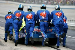 Crew members for Kyle Busch push the car to the garage after having engine troubles