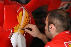 A Scuderia Ferrari mechanic touches up the sticker work