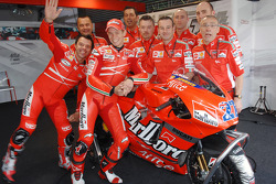 Loris Capirossi and Casey Stoner pose with Ducati team members