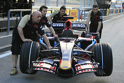 Red Bull Racing team members push the car on pitlane