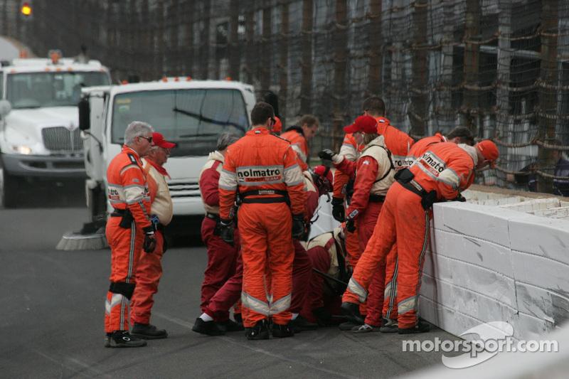 Mitglieder der Sicherheitsstaffel überprüfen die Schäden nach dem Unfall von Josef Newgarden