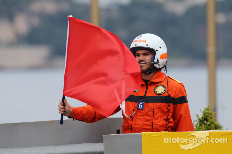 Marshal waves a red bendera as the session is stopped