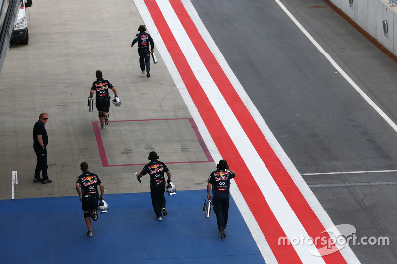 Red Bull Racing mechanics run to the pit lane entrance