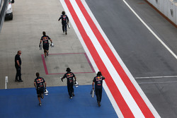Red Bull Racing monteurs lopen naar de ingang van de pits