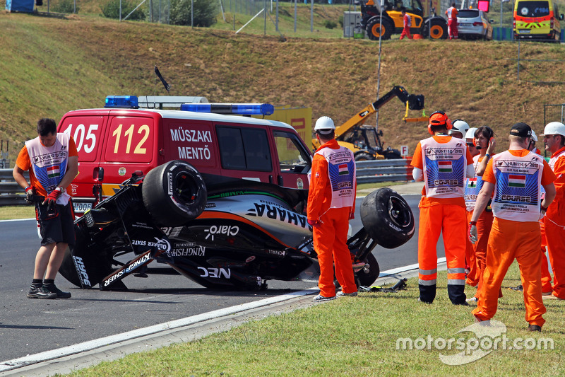 Safety crews tend to the crashed car of Sergio Perez, Sahara Force India F1