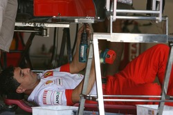 A Scuderia Ferrari team member works on the car