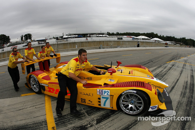 Penske Racing team members push the Porsche RS Spyder back to the paddock area