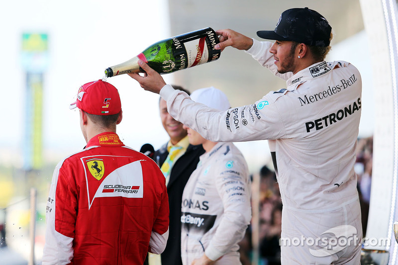 Race winner Lewis Hamilton, Mercedes AMG F1 celebrates on the podium with third placed Sebastian Vettel, Ferrari