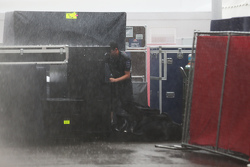 A Mercedes AMG F1 mechanic struggles in the paddock during a thunderstorm that cancelled FP2