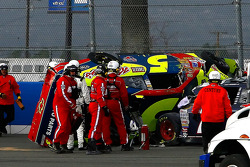 Safety personel work to free Casey Mears from his wrecked car at the exit of turn 2 after a crash