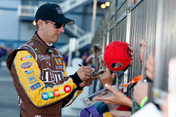 Kyle Busch signs autographs after winning the pole