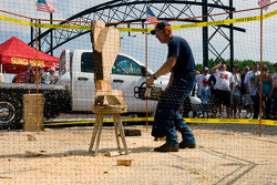 A sculptor makes art work by sawing wood as NASCAR fans watch him in Victory Plaza
