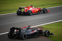 El McLaren MP4-30 de Fernando Alonso, McLaren  pasa por Sebastian Vettel, Ferrari en la segunda sesión de práctica