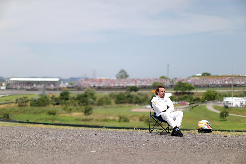 Фернандо Алонсо, McLaren, відпочиває за межами траси після поломки машини