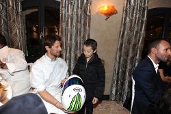 Romain Grosjean remet un casque à un jeune enfant