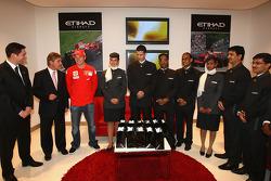 Kimi Raikkonen of Ferrari poses with Etihad staff at the opening of the Etihad Holiday Store at Marina Mall