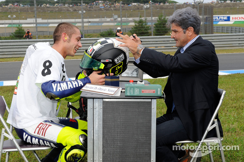 Juara dunia MotoGP 2008, Valentino Rossi, menandatangani helm khususnya