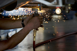 Sparks fly as a Joe Gibbs Racing Toyota crew member works on the car of  Joey Logano