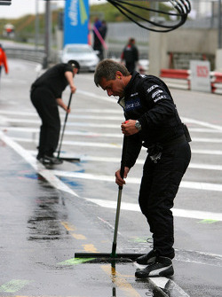 Mercedes mechanics cleaning the pitlane in front of the pitboxes