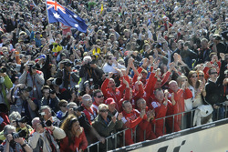 Fans and team members celebrate during podium ceremony
