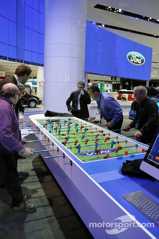 Des membres de l'équipe Ford et des médias s'affrontent dans un match de baby-foot improvisé sur le