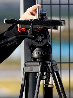 A small camera on a large tripod