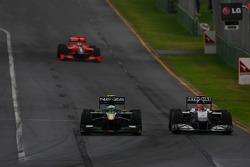 Heikki Kovalainen, Lotus F1 Team and Michael Schumacher, Mercedes GP
