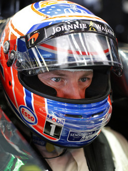 Jenson Button, McLaren MP4-31 sits with crash helmet on in the cockpit