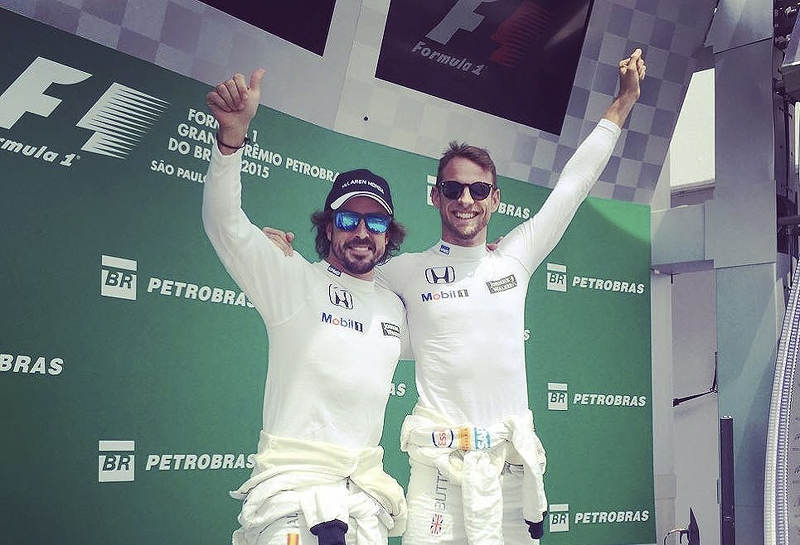 Fernando Alonso y Jenson Button bromean simulando un doblete de McLaren sobre el podio de Interlagos